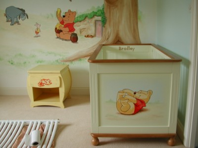 Painting on a cot to match childrens' mural