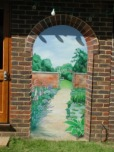 Creating a view in the garden by fixing a trompe l'oeil panel to a wall